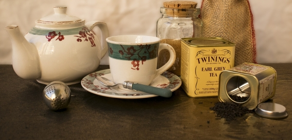 Teapot, steeping ball, teacup, and tin of Twinings Earl Grey teabags